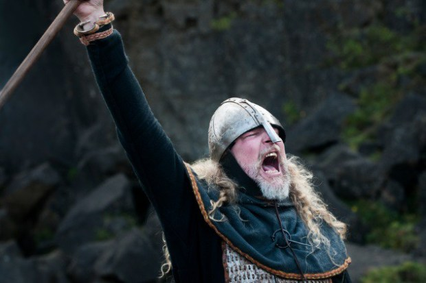 Partial view of a Viking male reenactor with long blond hair under a metal helmet dressed in full warrior armour and battle gear with raised weapon yelling a victory cry in battle in the historic location where Vikings once assembled annually to recite and discuss laws, Pingvellir, Iceland