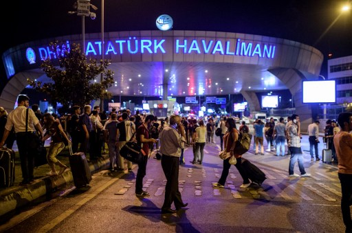 EDITORS NOTE: Graphic content / People stand outside the entrance as they leave the airport after two explosions followed by gunfire hit the Turkey's biggest airport of Ataturk in Istanbul, on June 28, 2016. At least 10 people were killed on June 28, 2016 evening in a suicide attack at the international terminal of Istanbul's Ataturk airport, Turkish Justice Minister Bekir Bozdag said. Turkey has been hit by a string of deadly attacks in the past year, blamed on both Kurdish rebels and the Islamic State jihadist group. / AFP PHOTO / OZAN KOSE